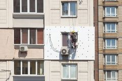 Muri l'isolamento termico, la scalata industriale, il lavoro ad alta altitudine, l'isolamento delle pareti con la plastica della  Fotografia Stock