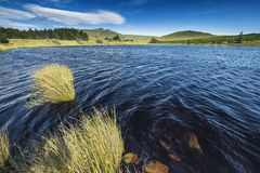 Murky Lake in Snowdonia National Park. Dark water of Tryweryn Lake at bright sunny day. Snowdonia National Park in North Wales, United Kingdom Stock Photography