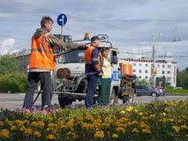 Murmansk, Russland - 21. Juni 2013, Angestellte von den städtischen Dienstprogrammen, die den Rasen auf dem Quadrat in der Stadt  lizenzfreies stockfoto