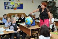 Murmansk Ryssland - September 17, 2013, barn som studerar geografi i klassrumet genom att använda jordklotet royaltyfri fotografi