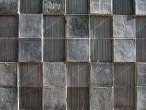 Muro de cemento gris con el modelo cuadrado geométrico y texturas apenadas imagen de archivo