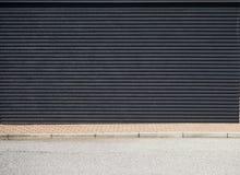 Muro de cemento negro con rayas horizontales, una acera marrón de la teja y una carretera de asfalto delante de ella imagenes de archivo