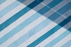 Muro de cimento pintado com as listras e sombras azuis e azuis diagonais imagem de stock