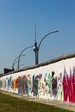 Muro di Berlino con la torretta della televisione e dei graffiti Fotografia Stock
