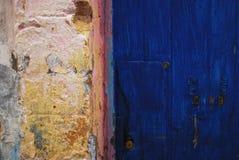 Muro di cemento variopinto luminoso e una porta blu Fotografia Stock Libera da Diritti