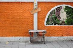 Muro di mattoni arancio sulla via Immagine Stock