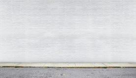 Muro di mattoni bianco sulla via Immagine Stock