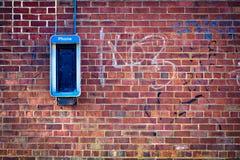 Muro di mattoni con il telefono a gettone fotografia stock libera da diritti