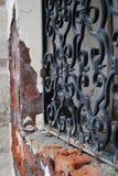 Muro di mattoni con la finestra antica del ferro Fotografie Stock