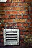 Muro di mattoni con la griglia del metallo Fotografia Stock