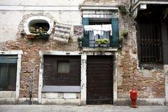 Muro di mattoni con le finestre ed i portelli Fotografia Stock