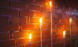 Muro di mattoni dell'argilla illuminato con le lampade di pavimento fotografie stock