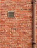 Muro di mattoni di Brown con lo sfiato ed il vecchio tubo Immagini Stock