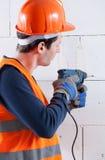 Muro di mattoni di perforazione del costruttore Immagine Stock