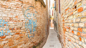 Muro di mattoni lungo la via di camminata a Venezia Immagini Stock