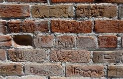 Muro di mattoni rosso con i nomi multipli cesellato nel mattone immagini stock libere da diritti