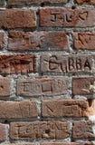 Muro di mattoni rosso con i nomi multipli cesellato nel mattone immagini stock