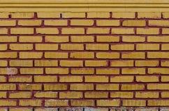 Muro di mattoni rosso con l'arancia, dante un tono giallastro fotografie stock