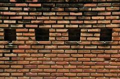 Muro di mattoni rosso con le tenute del quadrato per fondo. Fotografie Stock