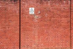 Muro di mattoni rosso con un segnale di pericolo Fotografia Stock Libera da Diritti