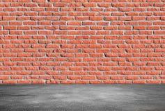 Muro di mattoni rosso e pavimento grigio dell'asfalto fotografia stock
