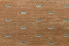 Muro di mattoni rosso originale con le piccole finestre come fondo Fotografie Stock
