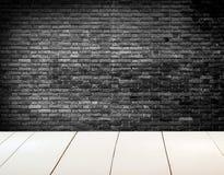 Muro di mattoni strutturato in bianco e nero Grungy con il pavimento di legno bianco Immagine Stock