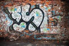 Muro di mattoni urbano con i graffiti caotici grungy Fotografia Stock Libera da Diritti