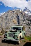 MURREN, SUÍÇA - 27 DE MAIO DE 2017: Um jipe do verde do vintage com o fundo suíço majestoso dos cumes Fotos de Stock
