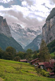 Murren in the swiss Alps. Murren  in the swiss Alps, in a valley with rural houses, in the background are mountains  on a cloudy day.It´s a vertical picture Stock Photography