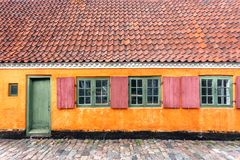 Murs colorés dans la maison de style traditionnel à Copenhague, Danemark Façade d'immeuble de brique historique avec le toit de t images stock