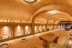 Murs de briques de vieil établissement vinicole de Khareba de cave avec beaucoup de bouteilles dans la pièce fraîche souterraine images stock