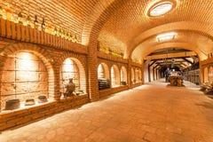 Murs de briques de vieil établissement vinicole de Khareba de cave avec beaucoup de bouteilles dans la pièce fraîche souterraine photographie stock libre de droits