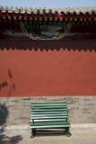Murs rouges de parc, la chaise verte Photographie stock