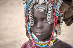 Mursi Girl with rich head decoration. TURMI, ETHIOPIA - AUGUST10, 2014: portrait of ypung unidentified Mursi triba girle with tipical head decoration. Mursi stock photography
