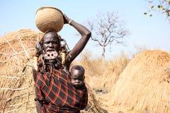 Mursi-Stammdame, die ihr Baby trägt stockfotos