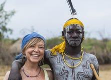 欧洲妇女和人从Mursi部落在Mirobey村庄 Mago 库存图片