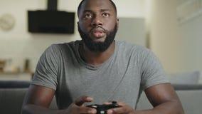 Murzyn bawić się gra wideo w domu Portret czarnego faceta mienia sztuki stacja zdjęcie wideo