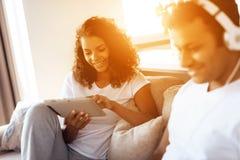 Murzyn i kobieta siedzimy na leżance Mężczyzna pracuje na laptopie, kobieta czyta coś na pastylce Zdjęcie Stock