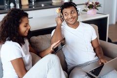 Murzyn i kobieta siedzimy na leżance Mężczyzna pracuje na laptopie, kobieta czyta coś na pastylce Fotografia Royalty Free