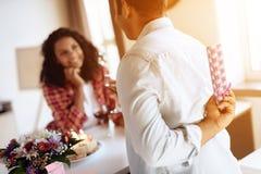 Murzyn i kobieta w kuchni w domu Mężczyzna przygotowywał prezent dla kobiety której wręcza ona, Fotografia Stock