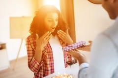 Murzyn i kobieta w kuchni w domu Mężczyzna przygotowywał prezent dla kobiety której wręcza ona, Obraz Stock