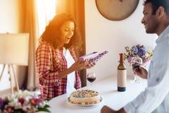 Murzyn i kobieta w kuchni w domu Mężczyzna przygotowywał prezent dla kobiety której wręcza ona, Zdjęcie Stock