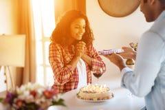 Murzyn i kobieta w kuchni w domu Mężczyzna przygotowywał prezent dla kobiety której wręcza ona, Fotografia Royalty Free