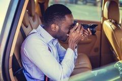 Murzyn używa dslr kamerę w samochodzie fotografia stock