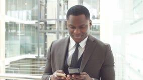 Murzyn używa jego telefon dla biznesu Amerykanina afrykańskiego pochodzenia biznesowy profesjonalista pracuje na jego telefonie k