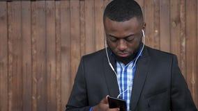 Murzyn w słuchawkach wyszukuje telefon komórkowego na ciemnym drewnianym tle zbiory