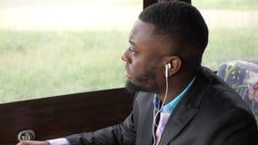 Murzyn wyszukuje smartphone obsiadanie w kawiarni jest słuchającym muzyką w słuchawkach zbiory