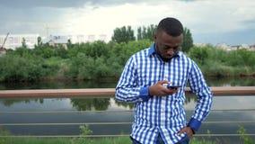 Murzyn wyszukuje telefonów spojrzenia przy kamerą i uśmiechów stojaki na nabrzeżu w parku zdjęcie wideo
