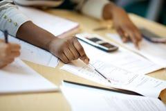 Murzynek pracy przez spreadsheets w spotkaniu zdjęcia stock